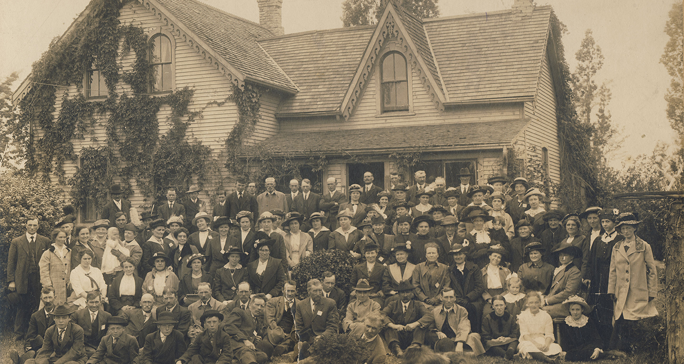 """Photograph depicting a large group of people gathered outside a house (wood siding). Photograph is mounted on cardstock matbaord; around the edges has been written in ink: """"about 1910 or 12, John Bowers farm, Women's Institute 15th Con. Huron Township."""""""